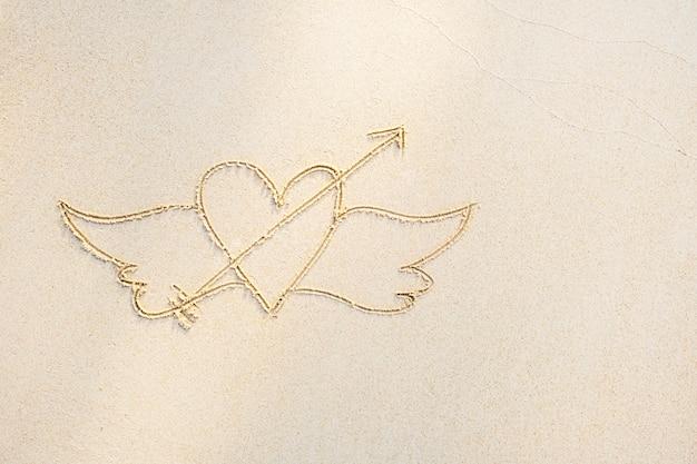 하얀 모래에 그려진 날개를 가진 심장, 가까이, 상위 뷰. 하얀 모래 배경, 복사 공간