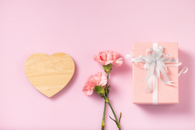 ギフトボックスとカーネーションの花、母の日とバレンタインデーのメッセージのために空のハート木製