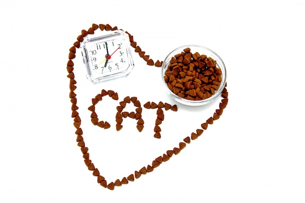 The heart and the word cat are lined with pieces of dry cat food. an alarm clock and a bowl of dry cat food inside this heart .