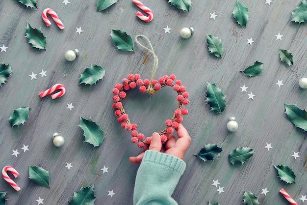 Венок-сердце украшен матовыми ягодами.