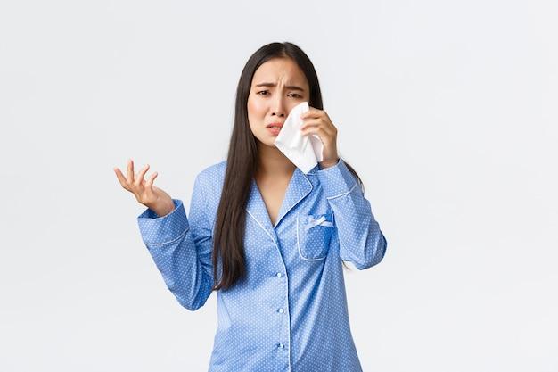 Убитая горем и подавленная азиатская девушка жалуется на измену парню во время ночевки, разговаривает с подругой, вытирает слезы дремотой, выглядит озадаченной и разочарованной, носит пижаму