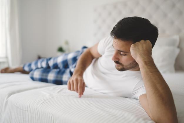 침대에 잠옷을 입은 상심한 외로운 남자