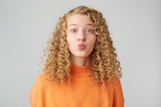 Heartful sweeet lovely curly blonde sends air kiss to a carmera, dressed in warm orange oversize sweater