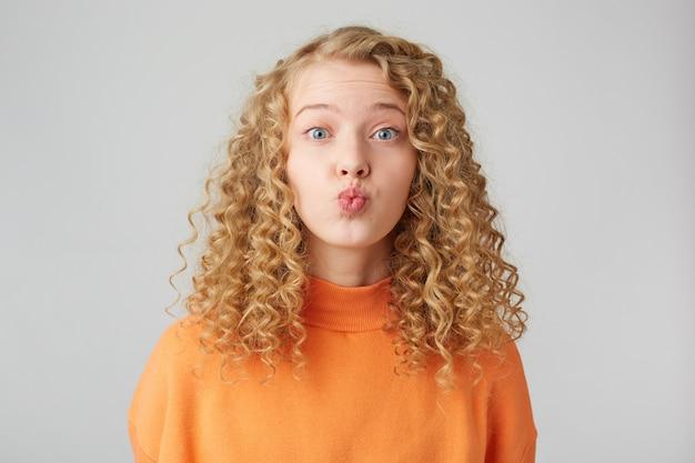 Милая кудрявая блондинка посылает воздушный поцелуй кармеру, одетой в теплый оранжевый свободный свитер