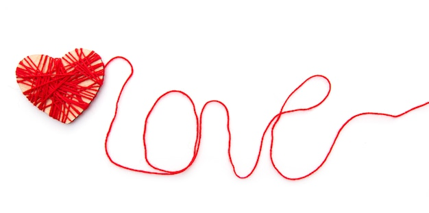 白い背景で隔離赤い糸で作られた囲炉裏と愛という言葉