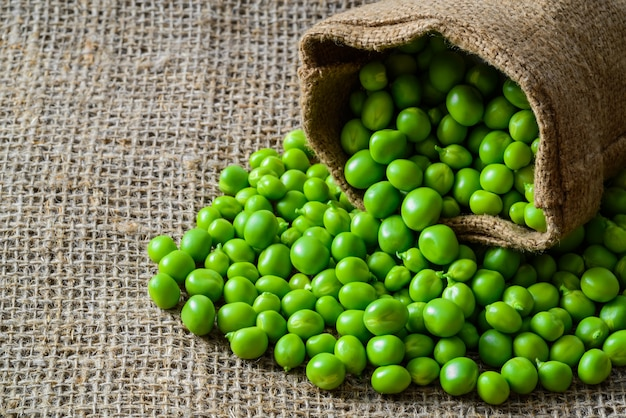 Hearthy fresh green peas and pods on rustic wood table.