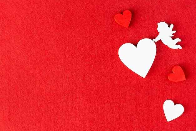 バレンタインデー、結婚式、またはデートの赤いフェルトの背景にハートとキューピッド