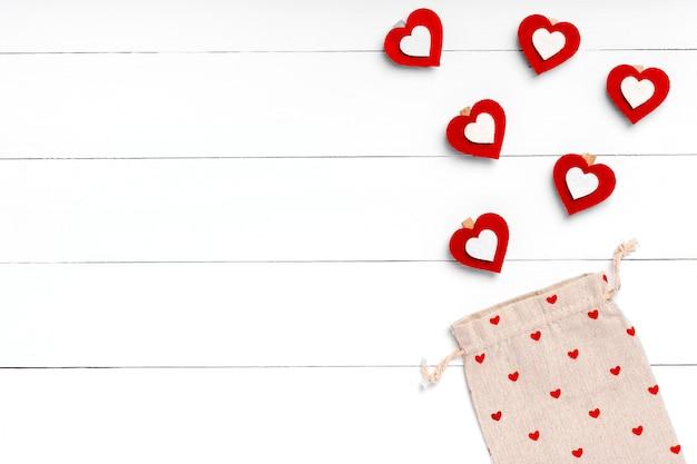 Сердца и ecobag на белой деревянной поверхности. день святого валентина концепция плоская планировка, вид сверху, сверху