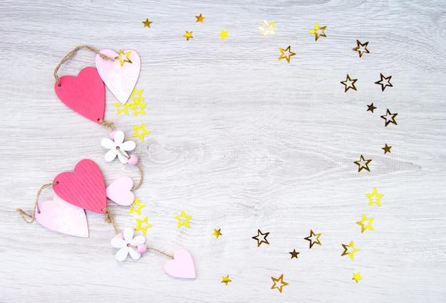 木製の背景にハートと星。母の日、3月8日のバレンタインデー。テキスト用のスペース。
