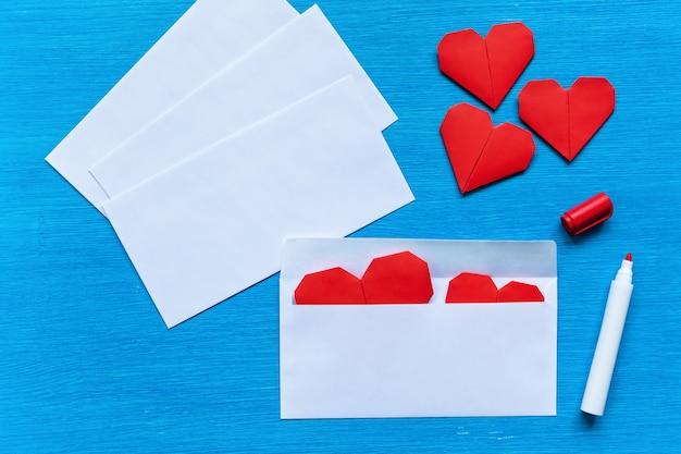 ハートはターコイズブルーのテーブルの白い封筒に入っています。封筒の中の心..
