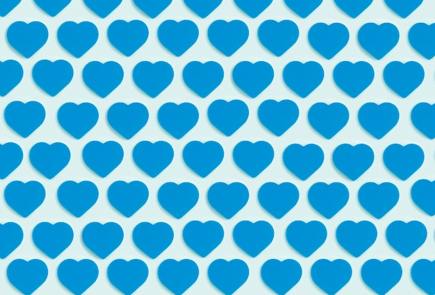 Hearts background. colored ornament pattern from cut out blue hearts on a blue background. love, romance, wallpaper, postcard minimal concept
