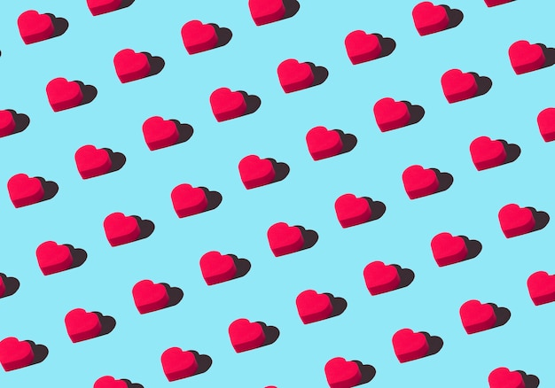 Hearts background. colored ornament pattern from cut out red hearts on a blue background. love, romance, wallpaper, postcard minimal concept
