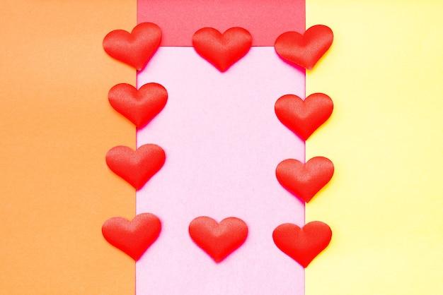 다양한 색상의 종이 사이에 로맨틱 한 프레임을 만드는 하트