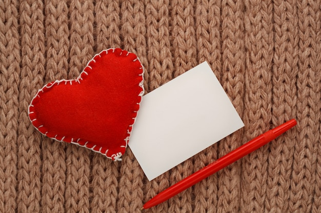 Hearts cut from fabric on a thread, on a knitted background. valentine day card