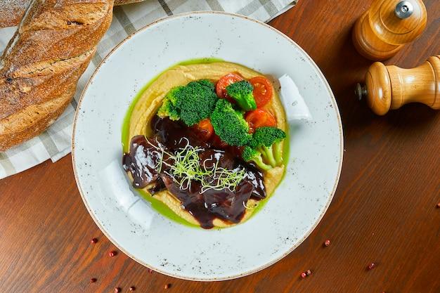 木製のテーブルに白い皿にマッシュポテト、ブロッコリー、トマトの形のおかずと照り焼きソースで揚げた心。健康食品。ウクライナ料理。平面図、フラットレイアウト