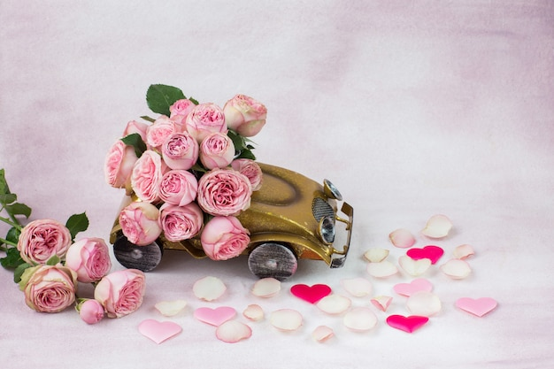 Hearts from satin, rose petals and a bouquet of pink roses in the car