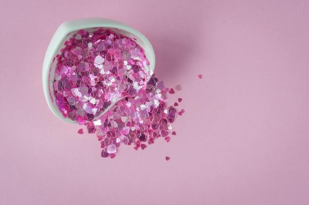 ピンクの背景にハートが光ります。幸せなバレンタインデー。コピースペース、フラットレイアウト。