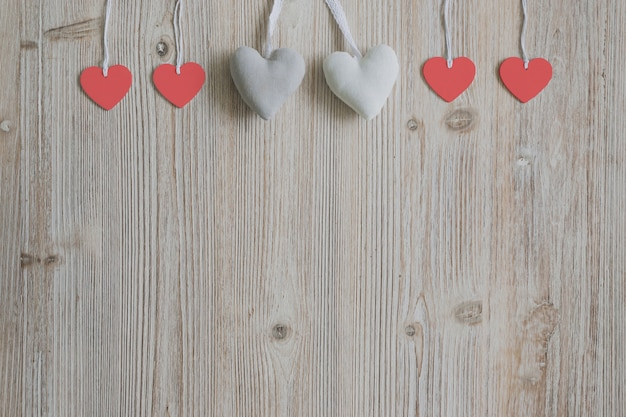 Hearts hanging from ropes on a wooden surface