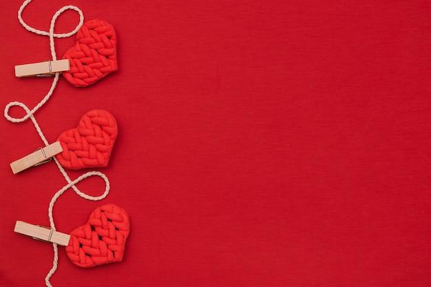 Сердца, висящие на красной стене. день святого валентина