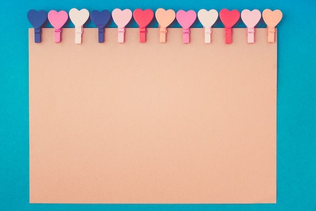 Hearts hold a note paper on a blue background