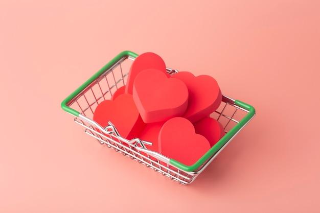 Сердца в тележке для покупок и супермаркета на цветном фоне. фон на день святого валентина (14 февраля) и любовь.