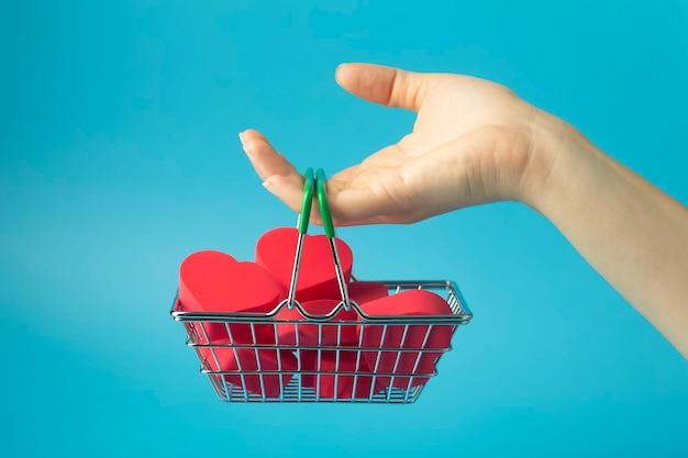 쇼핑 카트 ona 컬러 배경에 마음. 발렌타인 데이 (2 월 14 일)와 사랑의 배경.