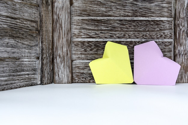 Hearts of lilac and yellow color of paper are on the background of a dark wooden board.
