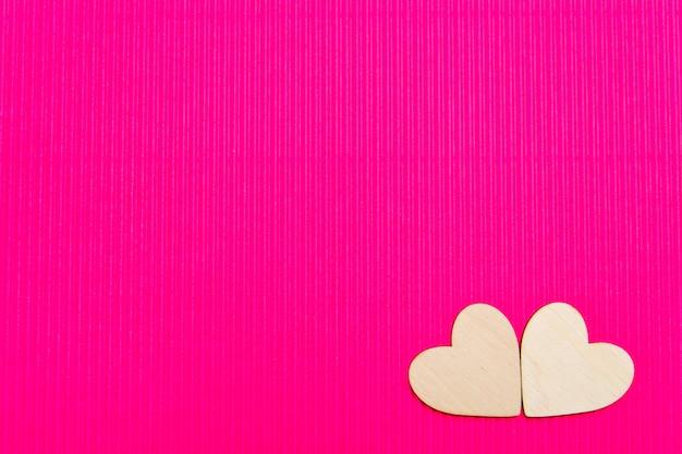 Сердца из дерева на розовом гофрированном фоне.
