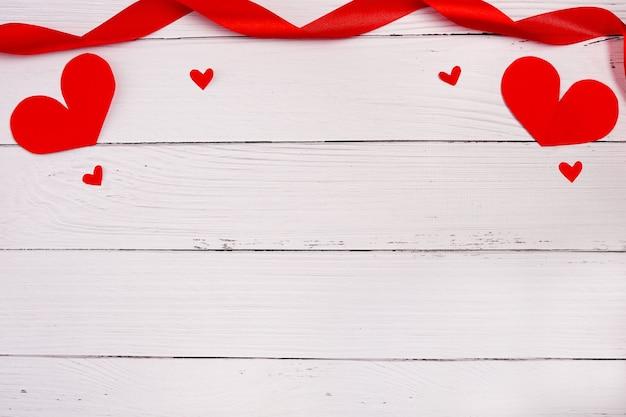白い木の背景の上の心。サントバレンタイン、母の日、誕生日グリーティングカード、招待状、お祝いのコンセプト。コピースペース