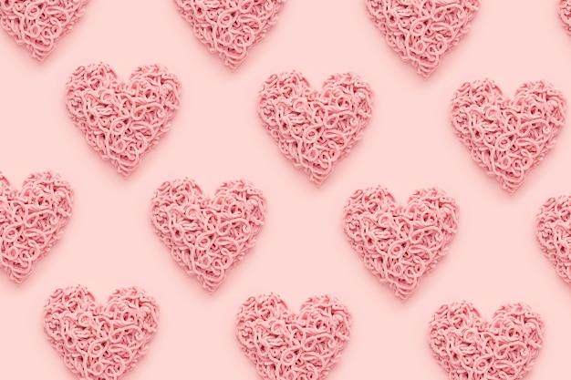 ピンクの背景、フラットレイのバレンタインデーのハートパターン。