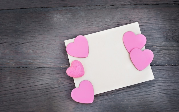 Hearts on a postcard with copy space on a wooden background. a sheet of paper with pink hearts on a dark wooden background