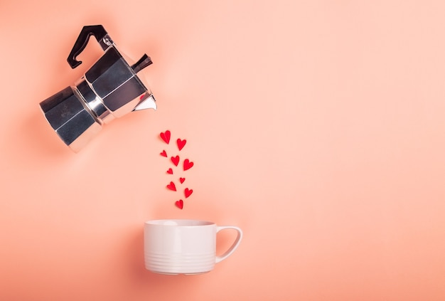 Hearts pouring from a geyser coffee maker into a cup. valentine's day concept. mininalist design. top view, flat lay, space for text.