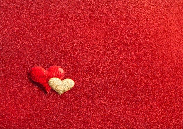 赤いテクスチャの光沢のある背景、休日のコンセプト、上面図に赤と金の心