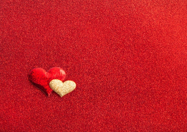Hearts red and gold on red textured shiny background, holiday concept, top view