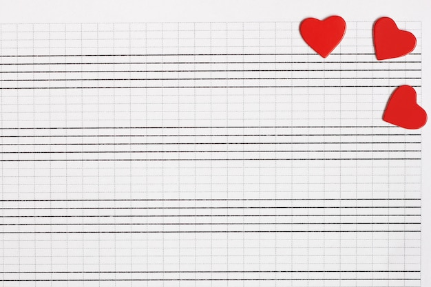Hearts of red paper lie on a clean music notebook. the concept of music and love.