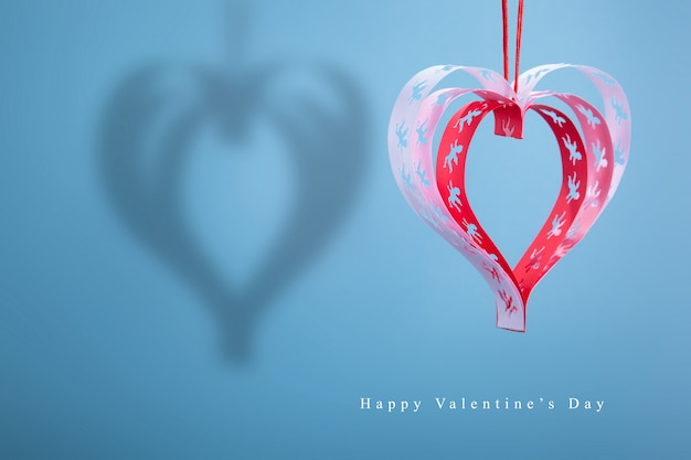 Hearts with handmade angels with shadow on a blue background, a good congratulatory card.