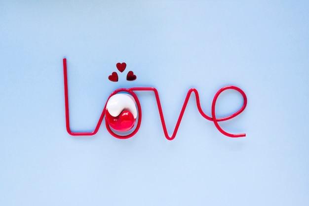 Hearts and yin and yang symbol near love writing