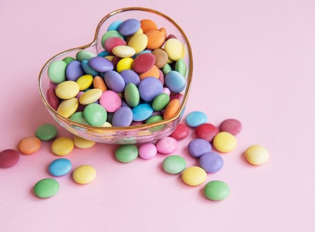 Чаша в форме сердца с разноцветными конфетами драже на розовой поверхности