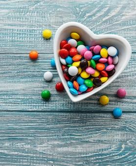 Чаша в форме сердца с разноцветными конфетами драже на деревянном фоне