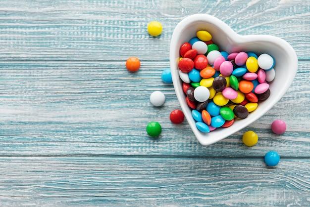 Чаша в форме сердца с разноцветными конфетами драже на деревянном столе