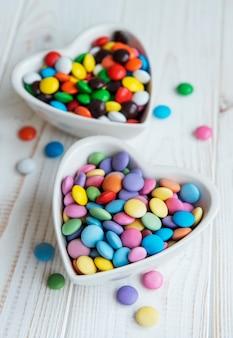Чаши в форме сердца с разноцветными конфетами драже на деревянной поверхности