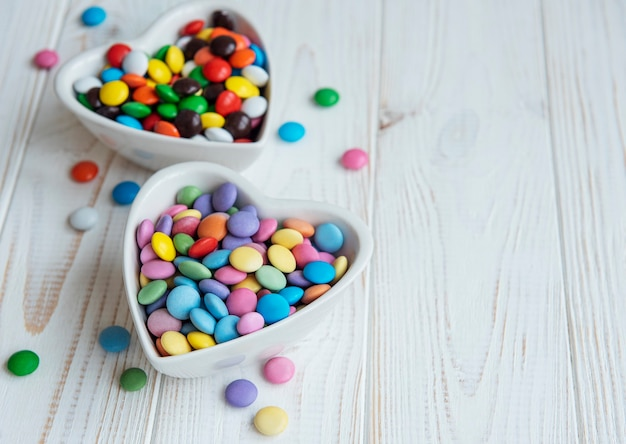 Heartshaped bowls with multicolored dragee sweets on a wooden  surface