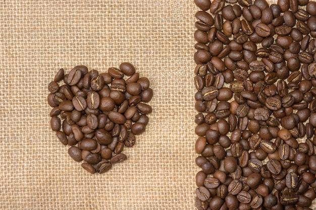Heartshaped coffee beans on a hemp sack flat lay