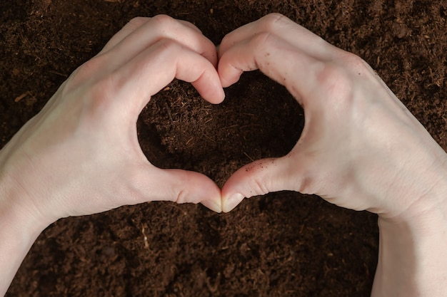 A heartshaped hands on the ground. earth day. planet earth.