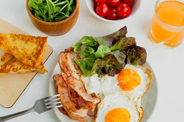 Hearty breakfast. fried eggs, bacon, lettuce, cherry tomatoes and toast. top view