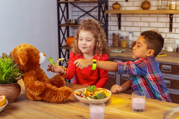 Hearty meal. cute girl keeping smile on her face while spending dinner time in kitchen with friend