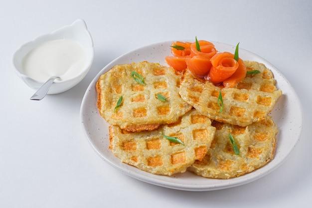 Сытные картофельные оладьи с красной рыбой, украшенные свежим зеленым луком. блюдо на белой тарелке.