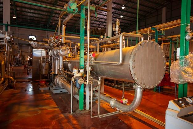 공장에서 반짝이는 스테인리스 화학 물질이 흐르는 파이프라인의 공정 영역에 있는 단열재의 열교환기.