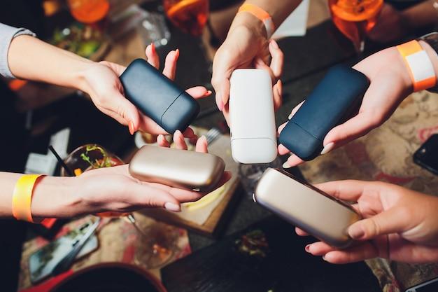 Технология производства табачных изделий без перегрева. женщина, держащая в руке электронную сигарету перед курением.