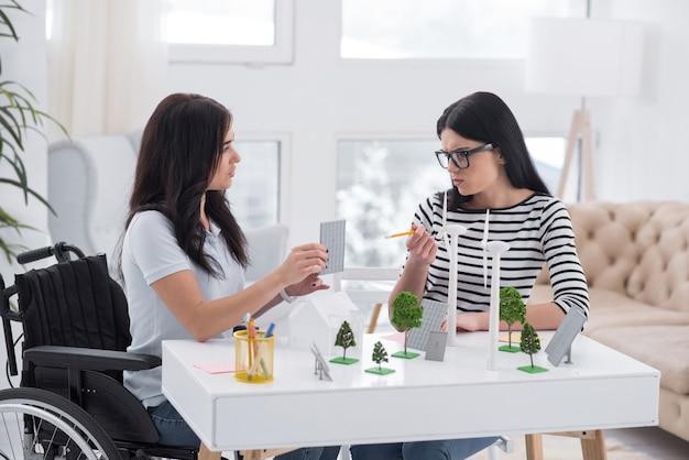 熱く議論。反射障害のある女性と同僚が会話をし、代替エネルギーモデルを使用している